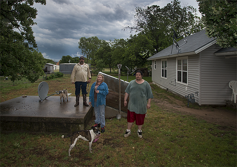 "Dennis Mann, left, and his wife Deborah stand outside their storm cellar with neighbor Mathew Tettleton moments after a tornado warning ended on Monday May 20, 2013, in Montague, Texas. When I asked Deborah if they had gone to the cellar she laughed and said, ""I did, but Dennis stayed out here to make sure his truck didn't blow away.""  ©2013 Robert W. Hart"