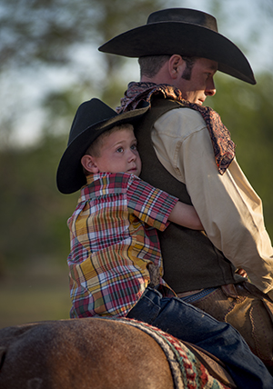 A young Albany, Texas cowboy holds tight to his dad after the conclusion of the Fort Griffin Fandangle Sampler on May 4, 2013 at the site near Fort Griffin where Doc Holliday and Wyatt Earp met. ©2013 Robert W. Hart
