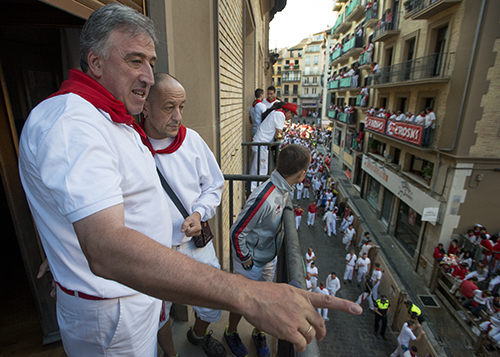 Pamplona Alcalde Joseba Asirón, left,  prepares to watch the running of the bulls from the city hall building in Pamplona, Spain on Friday July 10, 2015.